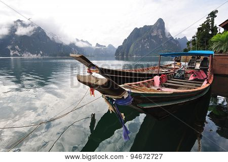Long tailed boat floating on lake