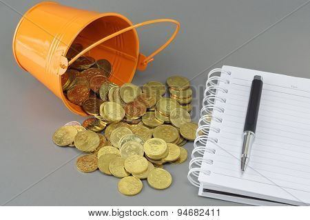 Gold Coins Notepad And Bucket - Business Concept