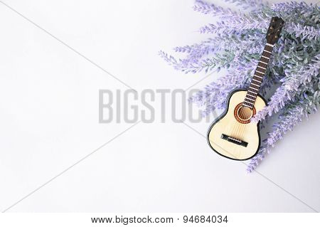 The acoustic guitar on a lavender brunch background