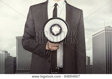 Businessman holding megaphone on cityscape background