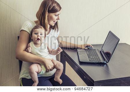The Mother Of The Woman With The Child On Hands At Work Behind The Laptop