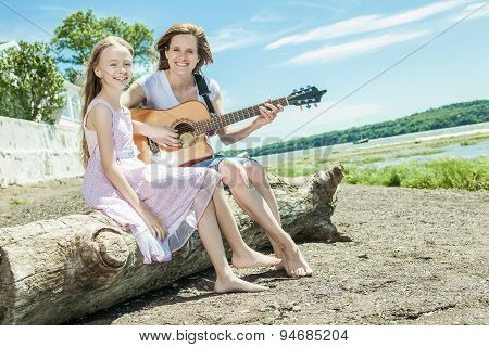mother and daughter on the side of the beach play guitar
