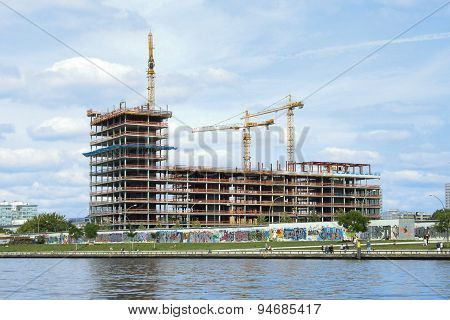 building construction site with cranes and scaffolding