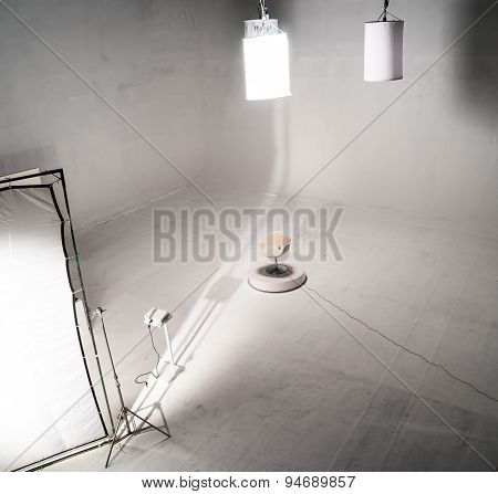 White Empty Chair In White Studio With Lighting Equipments