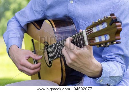 Young Male Playing A Classic Guitar Outside