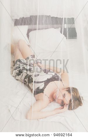 Pretty  woman  resting in bed behind transparent textile