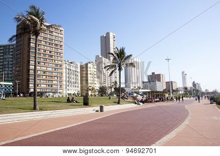 People On Beach Front Promenade Against City Skyline