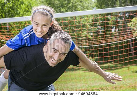 teenager girl with his father play soccer in a beautiful day