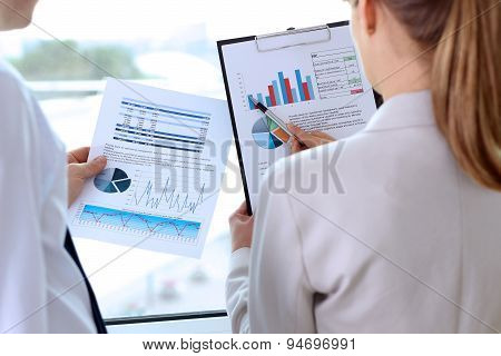 Image Of Business Partners Discussing Documents, Graphs At Meeting