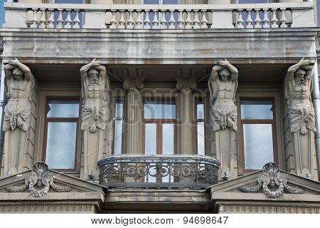 Four Statues Hold The Veranda Of A Building