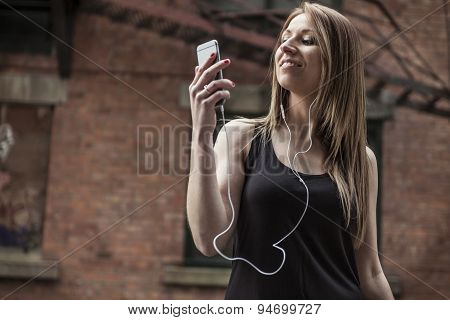 young beautiful woman in town listening music earphone