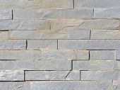 foto of cleaving  - wall of rough natural marble gray stone with the cleaved surface laid horizontally like a brick - JPG