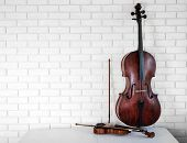 stock photo of cello  - Cello and violin on bricks wall background - JPG