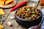 foto of cilantro  - vegetarian chili with cilantro on a dark wood background - JPG