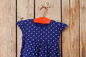 picture of habilis  - Child dress on hanger on wooden wall background - JPG