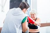picture of sparring  - Senior woman with trainer in boxing sparring hitting sandbag - JPG