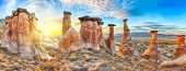 foto of chimney rock  - Rocks looking like mushrooms dramatically lit by a sunset in Cappadocia - JPG