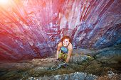 picture of climbing wall  - female rock climber climbs on a rocky wall she keeps a hand on the rock and laughs - JPG