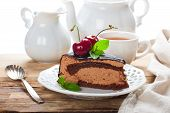 image of high calorie foods  - Piece of delicious chocolate mousse cake with cherries and mint over white - JPG