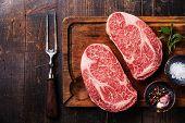 image of ribeye steak  - Two Raw fresh marbled meat Black Angus Steak Ribeye seasonings and meat fork on dark wooden background - JPG