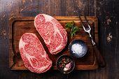 picture of ribeye steak  - Two Raw fresh marbled meat Black Angus Steak Ribeye seasonings and meat fork on dark wooden background - JPG