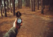 pic of pov  - Hiker woman searching direction with a compass in the forest - JPG