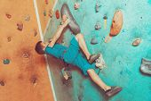 stock photo of climbing wall  - Free climber little boy climbing artificial boulder on practical wall in colorful gym - JPG