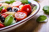 picture of basil leaves  - Caprese. Caprese salad. Italian salad. Mediterranean salad. Italian cuisine. Mediterranean cuisine. Tomato mozzarella basil leaves black olives and olive oil on wooden table. Recipe - Ingredients ** Note: Shallow depth of field - JPG