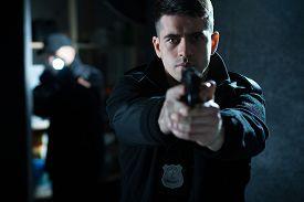 stock photo of handgun  - Image of a confident handsome policeman holding a handgun - JPG