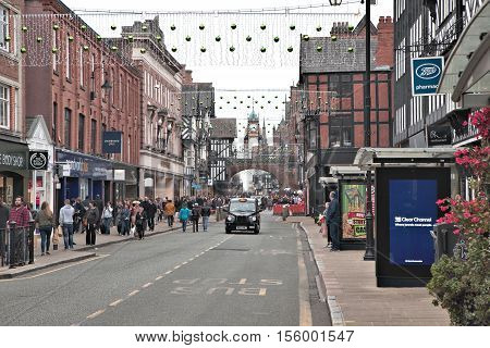 Chester Cheshire UK - October 30 2016: Foregate street with traditional black english taxi cab. Chester Eastgate clock in background. Road is decorated with green baubles for Christmas 2016.