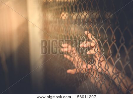 Hand holding on chain link fence vintage