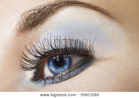 Beautiful woman`s open eye. Light blue and silver eye-shadows.