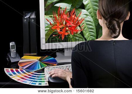 Diseñador en el trabajo. Muestras de color en la tabla. Cuadro vivo en el monitor de la computadora.