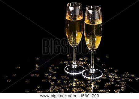 Champagne flutes and golden stars on black background