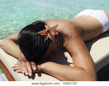 Beautiful  woman laying near the ocean and taking sunbath