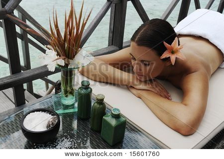 beautiful woman getting spa treatment at daylight near the ocean