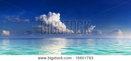 Panorama of turquoise lagoon and deep blue sky with clouds