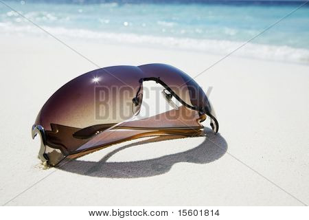 Sunglasses on white sand near the ocean