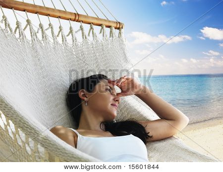 Beautiful woman lying in hammock near the ocean