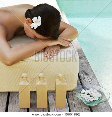 Hermosa mujer recibiendo tratamiento de spa junto a la piscina
