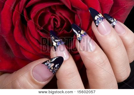 Elegant nail design. Woman hand with red rose.