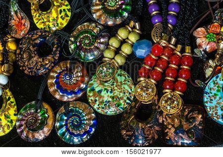 bead chaplet beading. a small piece of glass stone or similar material typically rounded and perforated for