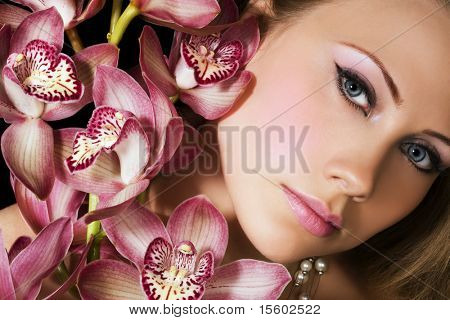 Portrait of woman with pink orchids