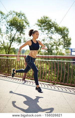 Attractive young woman doing sprint training in park