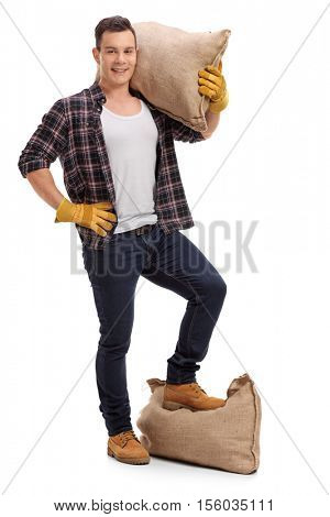 Full length portrait of a farmer with a burlap sack on his shoulder and under his foot isolated on white background