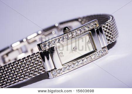 Elegant woman wristwatch on light violet background