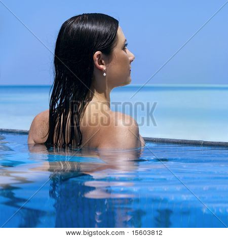 Young woman in swimming pool near the ocean