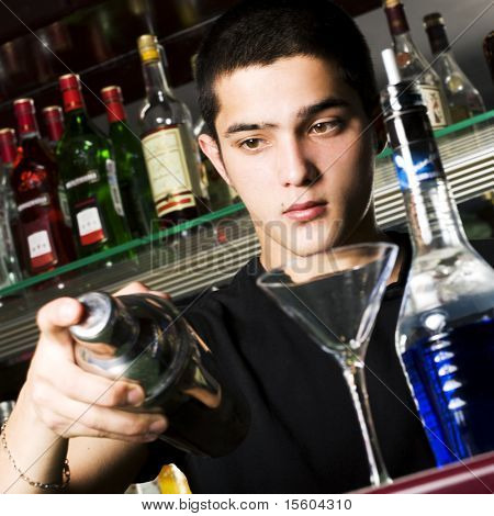 Barman with shaker making cocktail. Focus on face.