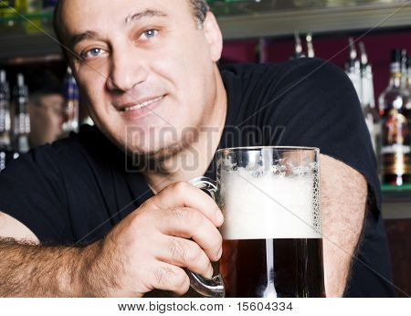 Man with beer in pub. Focus on glass and hand.