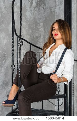 Young beautiful woman sitting on old round spiral staircase. Fashion shot